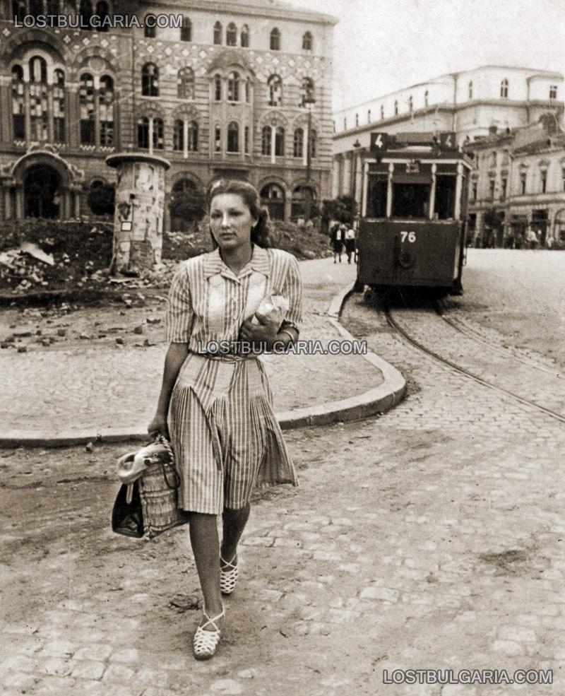 София 1944 г,. млада жена прекосява площада пред сградата на Духовната академия, отзад трамвай номер 4 и Съдебната палата