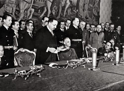 Министър-председателят проф. Богдан Филов чете реч на подписването за присъединяване на България към Тристранния пакт, присъстват още пълномощният министър в Берлин Първан Драганов (прав, втори от ляво), до него Димитър Шишманов (главен секретар на Министерството на външните работи), седящи от ляво на дясно: Хироши Ошима - посланик на Япония в Германия, външният министър на райха Йоахим фон Рибентроп, граф Галеацо Чано, унгарският посланик Döme Sztójay и други, Виена, двореца Белведере, 1 март 1941 г.